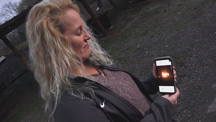 Anna Dobos shows a photo of the burning home where she used a hammer to save an 85-year-old man
