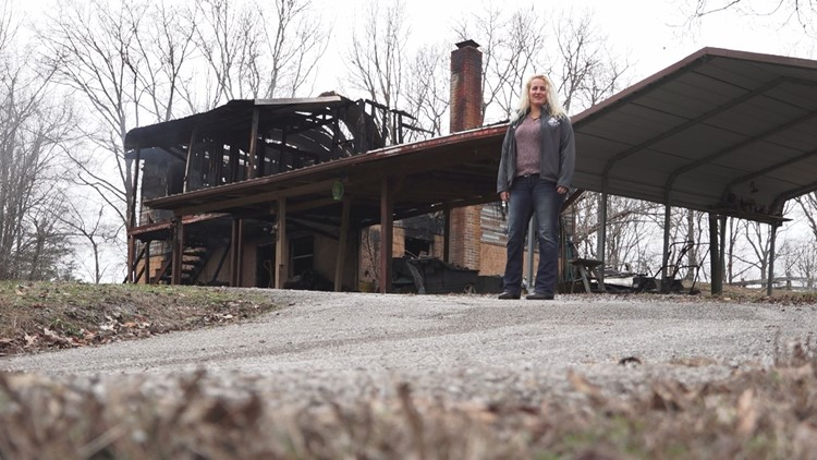 Anna Dobos stands in front of the burned home of Leroy Hallcox