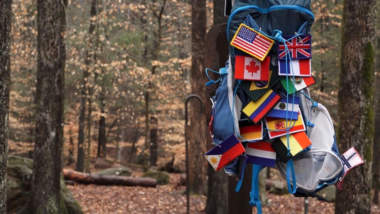 John Kelly running pack covered with flags of the home countries of the 2020 Barkley Marathons field