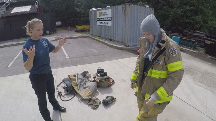 Rural Metro Firefighter Erin Gray shows 14-year-old Emilia Hoppe how to put on fire gear