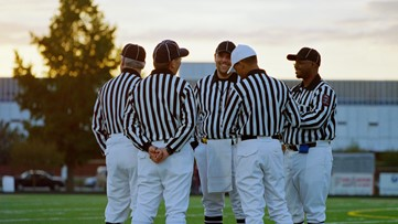 Why do referees wear black and white stripes?